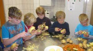 (vl.) Arne, Frauke, Paul, Leo und Max beim Kartoffeln schälen.